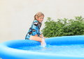 Wet little girl getting into pool in blue black white t shirt a blue Royalty Free Stock Images