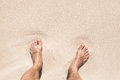 Wet male feet stand on white sand coastal Royalty Free Stock Image
