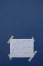Wet paint paper sign on blue wall a concrete Stock Photos