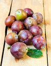 Wet plums on wooden surface Royalty Free Stock Image