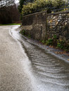 Wet road due to poor maintenance or drainage etc dangerous driving conditions budget cuts perhaps Stock Image
