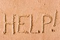 On the wet sand written the word help by sea Royalty Free Stock Image