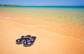 Wet sandals next to the sea. Royalty Free Stock Images