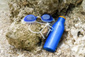Wet swimming goggles and suntan lotion lying on a rock. Royalty Free Stock Photo