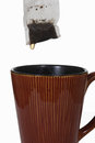 Wet tea bag above ceramic mug Royalty Free Stock Photo