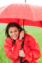 Wet young girl enjoying rainfall with umbrella in raincoat Royalty Free Stock Image