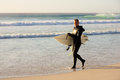 Wetsuit surfer carries surf board on beach near cape town south africa Royalty Free Stock Photo