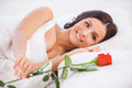 What a beautiful morning side view of young woman lying in bed with red rose Stock Image