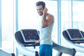 What did you say rear view of young handsome man in sportswear standing on treadmill in front of window at gym and adjusting his Stock Photo