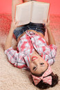 What an exciting book smiley young pin up girl lying on the carpet and reading a Royalty Free Stock Photo