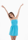 What a great day attractive young woman in blue dress holding her arms raised and smiling while standing isolated on white Stock Photos