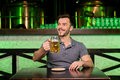 What a great day cheerful young man holding mug with beer and smiling while sitting in bar Royalty Free Stock Photos