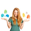 What house to choose red haired girl facing a choice isolated on a white holding coloured houses at her hands Royalty Free Stock Photography