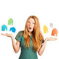 What house to choose red haired girl facing a choice isolated on a white holding coloured houses at her hands Stock Image