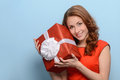 What is inside this box attractive young woman holding a gift b in her hands standing against blue background Royalty Free Stock Photography