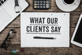 What Our Clients Say statement on notepad on office desk from ab Royalty Free Stock Photo