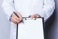 That is what you need close up of doctor pointing copy space on his clipboard while standing isolated on white Royalty Free Stock Photos