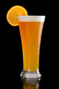 Wheat ale german style served on a dark bar with an orange slice on the rim Royalty Free Stock Images