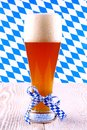 Wheat beer in glass with blue white ribbon checkered on bavarian background Royalty Free Stock Photo