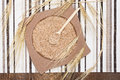 Wheat bran in bamboo plate and wooden spoon with wheat ears filled surrounded by on striped cloth napkin planks dietary Royalty Free Stock Photo