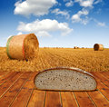 Wheat bread on the table straw bales in background Royalty Free Stock Photo
