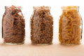 Wheat buckwheat and spelt pasta separated in three glass jars. Royalty Free Stock Photo