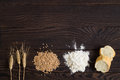 Wheat ears, grains, flour and sliced bread on a dark wooden table Royalty Free Stock Photo