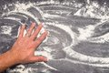 Wheat flour on grey working surface wiped away with male hand Royalty Free Stock Photo