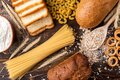 Wheat products on dark wooden background. Bread, spaghetti, wheat flour and flakes, loaf and dryings. Royalty Free Stock Photo