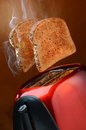 Wheat toast with smoke popping up from toaster two slices of healthy a red Stock Image