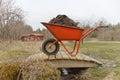 Wheel barrow full of mud orange standing on a small bridge Royalty Free Stock Photos