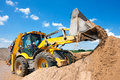 Wheel loader excavator unloading sand with water during earth moving works at construction site Royalty Free Stock Photo