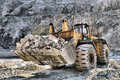 Wheel loader machine unloading rocks in the open mine of iron ore Royalty Free Stock Photography