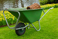 Wheelbarrel in a garden containing gardening tools standing on freshly mown lawn Stock Image