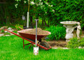 Wheelbarrow full of dirt with leaning shovel in garden a red sits a lush green as spring gardening work is underway Royalty Free Stock Photo