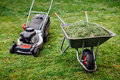 Wheelbarrow with grass and lawnmower on green lawn Royalty Free Stock Photo