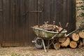 Wheelbarrow with logs standing near gate Stock Photo