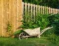 Wheelbarrow planter decorative wooden near wooden fence Stock Photo