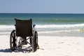 Wheelchair at beach empty sits vacant on a of sand with ocean waves and surf in the background Royalty Free Stock Images