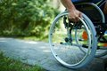 Wheelchair walk close up of male hand on wheel of during in park Stock Image