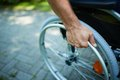 Wheelchair walk close up of male hand on wheel of during in park Royalty Free Stock Photo