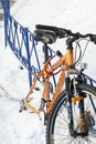 stock image of  Wheelless orange bicycle strapped to the iron fence