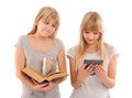 Which one ebook or book vs girl holding a big and her girlfriend reading an reader tablet device Stock Photo
