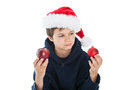 Which one teenage christmas boy looking confused holing a red organic apple and a red christmas ball he is wearing a dark blue Royalty Free Stock Image