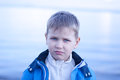 Whimsical boy by the seahore a handsome wearing blue jacket walking seashore Royalty Free Stock Photo