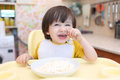 Whimsical little boy dont want to eat quark with sour cream on kitchen Royalty Free Stock Image