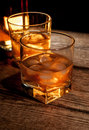 Whiskey or bourbon brown rum with ice on wood table Stock Photos