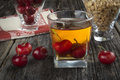 Whiskey cocktail with cherries and peanuts manhattan or other submerged next to it Stock Photography