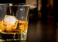Whiskey glass with ice in front of bottles with space for text Royalty Free Stock Photo