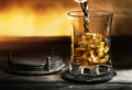 Whiskey glass of with ice on metal lining on background of yellow light Royalty Free Stock Images